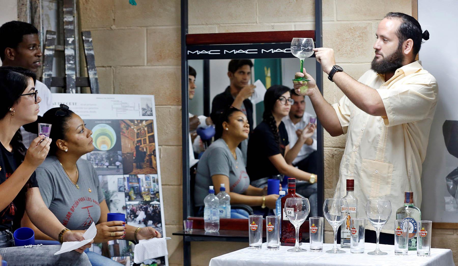 """Profesores y alumnos participan el jueves 31 de octubre en las clases sobre coctelería del proyecto comunitario """"Artecorte"""", en La Habana Vieja. Foto: Ernesto Mastrascusa / EFE."""