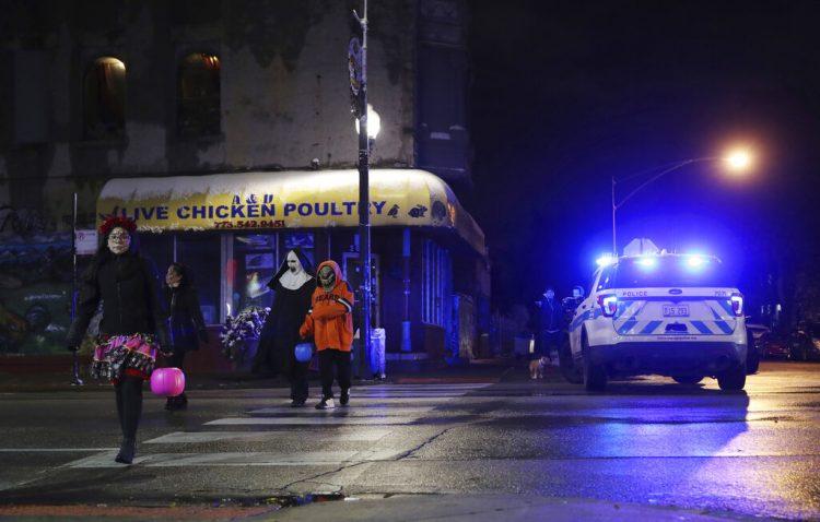 Personas disfrazadas que piden dulces por Halloween caminan en la calle 26 West junto al lugar donde una niña de 7 años fue baleada mientras hacía lo mismo, el jueves 31 de octubre de 2019, en Chicago. (John J. Kim/Chicago Tribune vía AP)