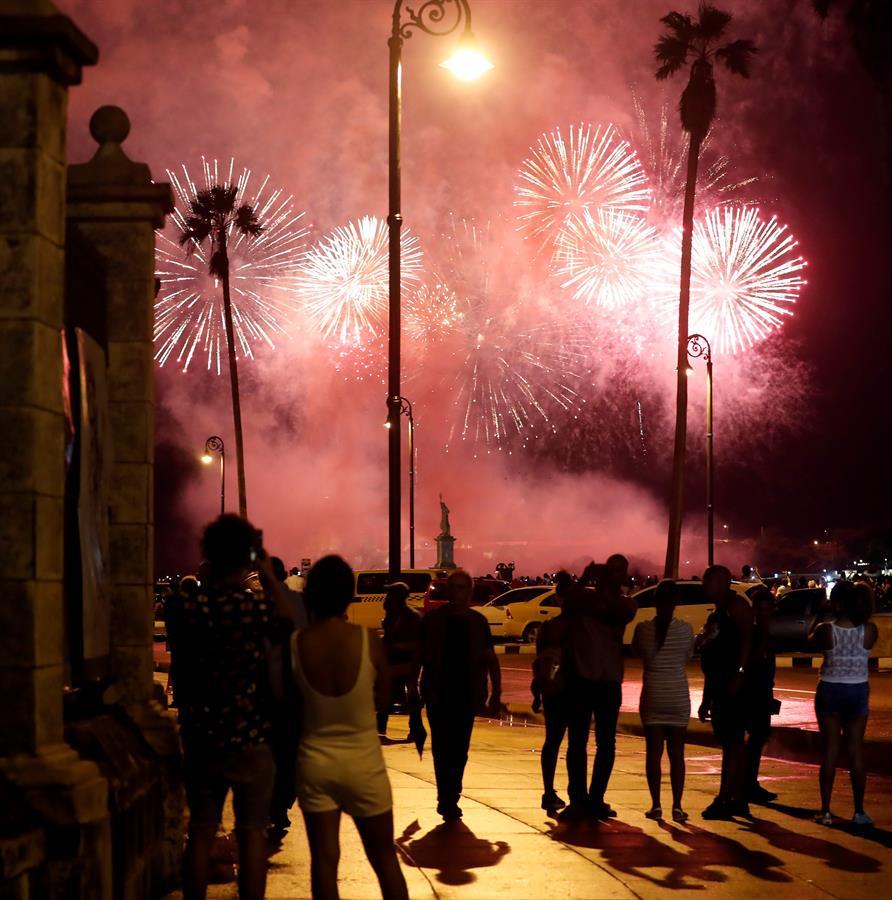 Personas observan el espectáculo de fuegos artificiales en La Habana, en vísperas del aniversario 500 de la ciudad. Foto: EFE/Ernesto Mastrascusa