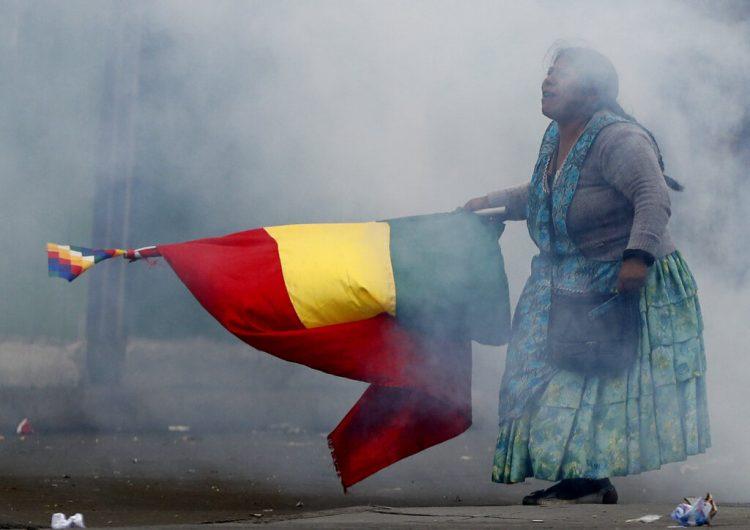 En esta imagen, tomada el 13 de noviembre de 2019, una seguidora del expresidente de Bolivia Evo Morales porta una bandera nacional durante disturbios con la policía, en La Paz, Bolivia. (AP Foto/Natacha Pisarenko)