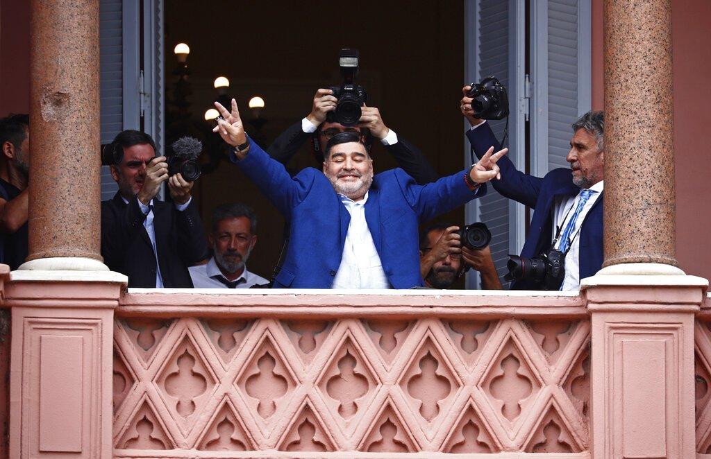 El ex gran futbolista Diego Maradona hace señales de victoria a los fanáticos en la casa del gobierno después de reunirse con el presidente argentino Alberto Fernández en Buenos Aires, Argentina, el jueves 26 de diciembre de 2019. Foto: AP/Marcos Brindicci
