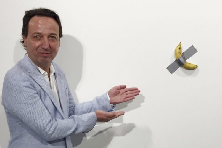 """En esta foto del 4 de diciembre del 2019, el dueño de galería Emmanuel Perrotin posa junto a la obra """"Comedian"""" del artista italiano Maurizio Cattlelan durante su exhibición en la feria Art Basel Miami, en Miami Beach, Florida. La obra se vendió por 120.000 dólares. (Siobhan Morrissey vía AP)"""