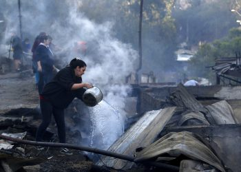 Residentes arrojan agua sobre los restos de sus casas el miércoles 25 de diciembre de 2019, después que un incendio dañó decenas de viviendas en las afueras de Valparaíso, Chile. Foto: Raul Zamora/Aton Chile vía AP.