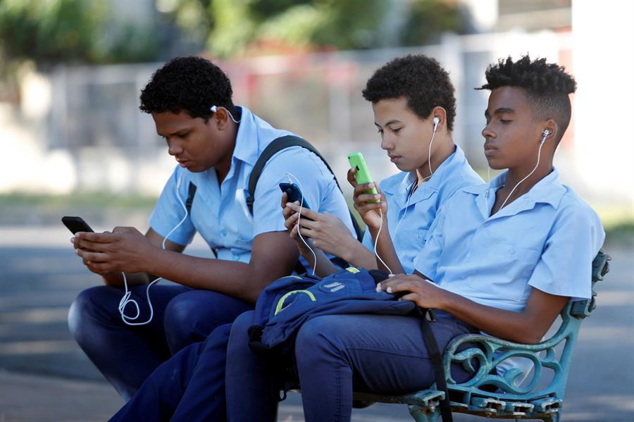 Un grupo de estudiantes usa su teléfono celular en un parque de La Habana. EFE/ Yander Zamora