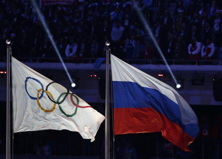 La bandera rusa ondea junto a la bandera olímpica durante la ceremonia de clausura de los Juegos Olímpicos de Invierno de 2014 en Sochi, Rusia.  Esta acusó al principal testigo de la Agencia Mundial Antidopaje (AMA) de modificar importantes datos de laboratorio. Foto: Matthias Schrader/AP.