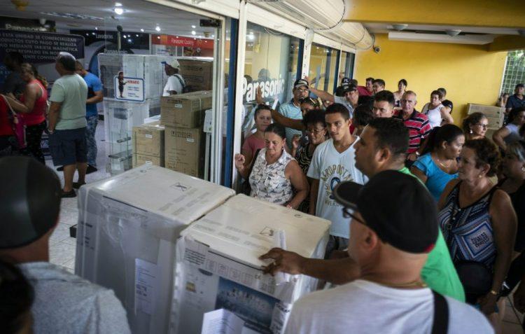Personas a la entrada de una tienda para la venta en moneda libremente convertible de equipos electrodomésticos en La Habana. Foto: AP / Archivo.