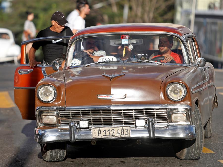 Un grupo de personas suben a un automóvil clásico que funciona como taxi, este lunes, en La Habana (Cuba). Foto: EFE/ Yander Zamora