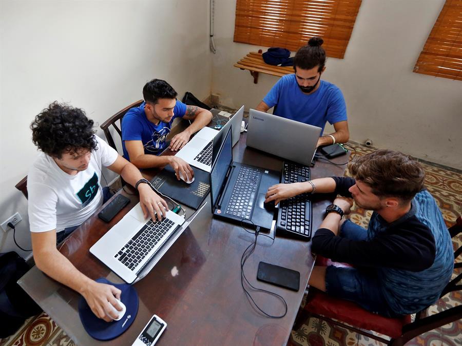 Fotografía del 03 de diciembre de 2019 de un grupo de desarrolladores de la app Sube quienes realizan labores en su oficina, en La Habana (Cuba). Foto: EFE/ Ernesto Mastrascusa