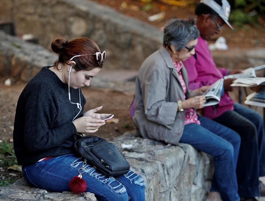 Una joven mira su teléfono celular una zona Wifi en La Habana. Foto: EFE/ Yander Zamora