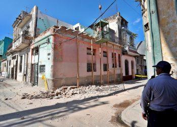 Un policía observa el martes 28 de enero de 2020, los trabajos en el lugar donde murieron tres niñas, de 11 y 12 años, al derrumbarse el balcón de un edificio en el barrio de Jesús María, en la Habana Vieja. Foto: Ernesto Mastrascusa / EFE.