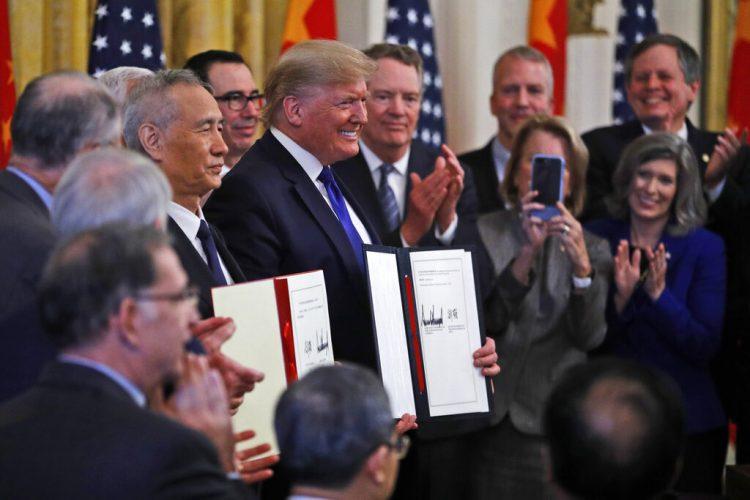 El presidente Donald Trump, centro, y el viceprimer ministro chino Liu He, izquierda, sostienen el acuerdo comercial después de haberlo firmado en la Sala Este de la Casa Blanca, el miércoles 15 de enero de 2020 en Washington. Foto: AP/Steve Helber