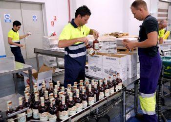 Trabajadores de Havana Club empacan botellas de ron en la línea de producción y llenado de la Fábrica de Ron de San José de las Lajas, en el occidente cubano, el 30 de enero de 2020. Foto: Ernesto Mastrascusa / EFE.