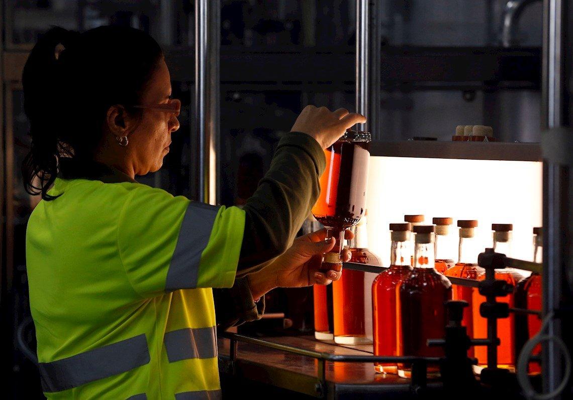 Una trabajadora realiza un examen de calidad a la línea de producción y llenado de ron, en la Fábrica de Ron de San José de las Lajas, en el occidente cubano, el 30 de enero de 2020. Foto: Ernesto Mastrascusa / EFE.