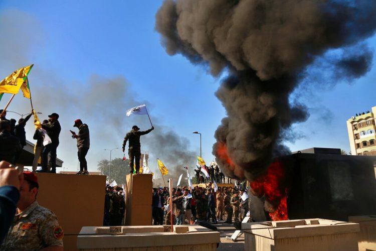 Manifestantes encienden una pira enfrente de la embajada de Estados Unidos en Bagdad, Irak, el martes 31 de diciembre de 2019. (AP Foto/Khalid Mohammed)
