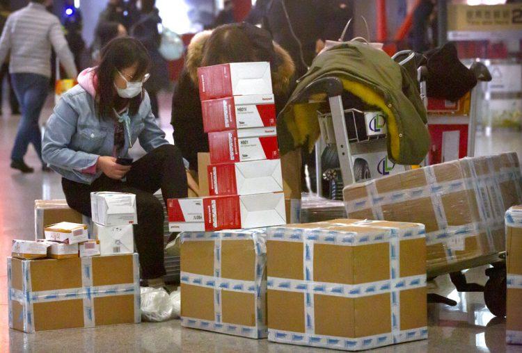 Una viajera sentada junto a cajas de mascarillas para la cara y respiradores en el aeropuerto internacional de Beijing, el 30 de enero de 2020. Foto: Mark Schiefelbein / AP.