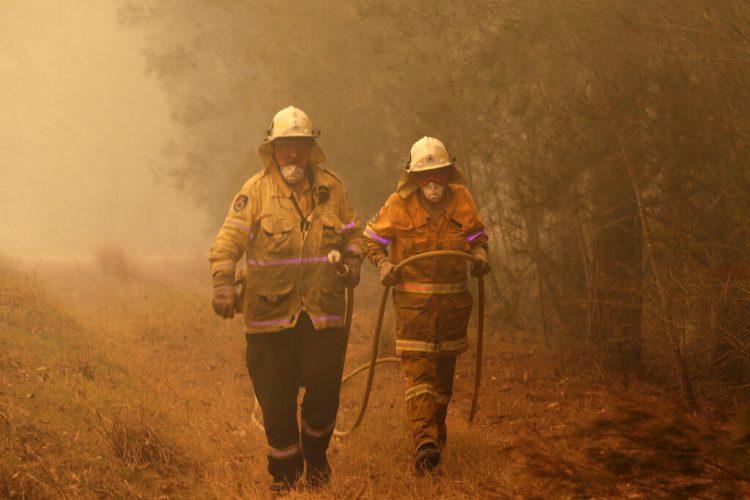 Dos bomberos arrastran una manguera de agua tras apagar un incendio cerca de Moruya, Australia, el 4 de enero de 2020. Foto: Rick Rycroft / AP.