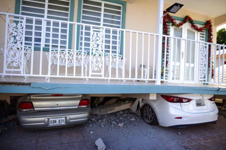 Una vivienda cayó sobre vehículos estacionados después de un terremoto registrado en Guánica, Puerto Rico, el lunes 6 de enero de 2020. Un sismo de magnitud 5,8 remeció Puerto Rico en la madrugada del lunes, provocando pequeños deslaves, cortes en el suministro eléctrico y graves grietas en algunas viviendas. (AP Foto/Carlos Giusti)