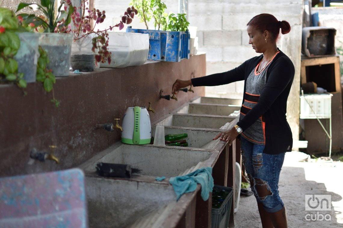 Nelvis Águila en los lavaderos comunales del interior donde se halla su vivienda en el municipio habanero de Regla, reconstruida tras el paso por La Habana del tornado de enero de 2019. Foto: Otmaro Rodríguez.
