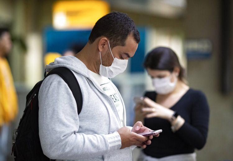 Pasajeros usando mascarillas como precaución contra el contagio del nuevo coronavirus usan sus teléfonos en el Aeropuerto Internacional de Sao Paulo, Brasil, el jueves 27 de febrero de 2020. Foto: Andre Penner / AP.