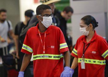 Los empleados del aeropuerto usan máscaras como precaución contra la propagación del nuevo coronavirus COVID-19 mientras trabajan en el Aeropuerto Internacional de Sao Paulo en Brasil, el miércoles 26 de febrero de 2020. Foto: Andre Penner / AP.