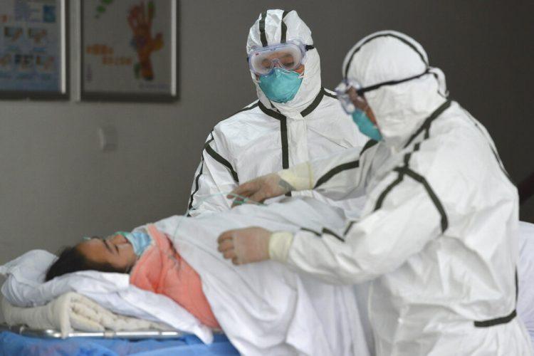 Personal sanitario provisto con trajes protectores traslada a una paciente infectada con coronavirus a un pabellón de aislamiento en el Segundo Hospital del Pueblo en Fuyang, provincia de Anhui, en el centro de China, a inicios de la pandemia. Foto: Chinatopix vía AP.