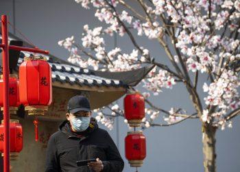 Un hombre que porta una mascarilla para protegerse del nuevo coronavirus observa junto a un decorado que promueve una película en Beijing, China, el miércoles 19 de febrero de 2020. Foto: Ng Han Guan/AP.