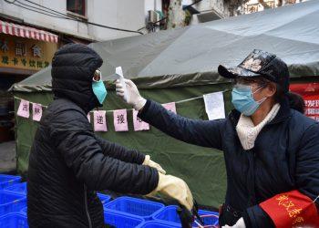 Una mujer revisa la temperatura a un ciclista que porta una mascarilla en la ciudad de Wuhan. Foto: Chinatopix vía AP/Archivo.