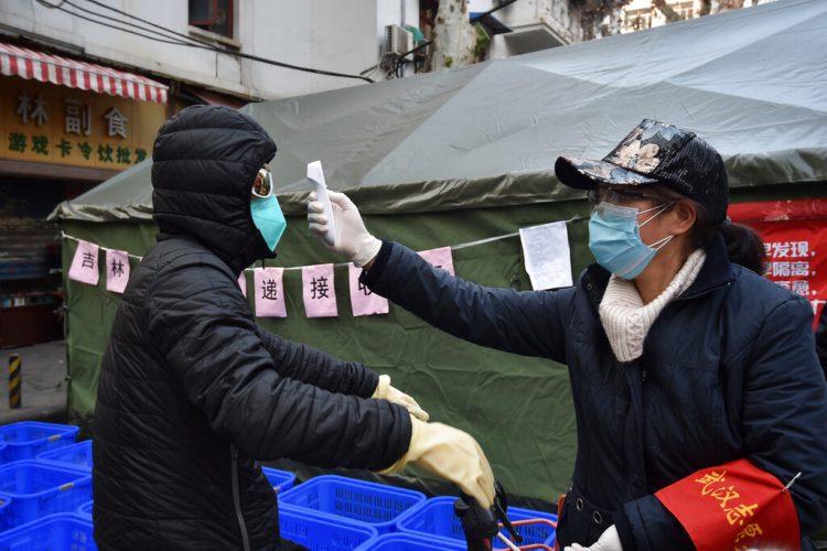 Una mujer revisa la temperatura a un ciclista que porta una mascarilla en la ciudad de Wuhan, el 21 de febrero de 2020. Foto: Chinatopix vía AP.