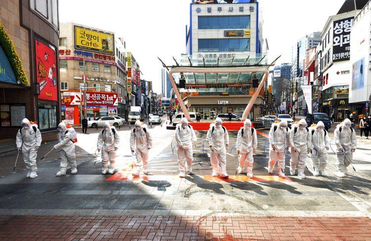 Soldados surcoreanos con vestimenta protectora rocían desinfectante para impedir la propagación del virus del COVI-19 en una calle en Dargu. Corea del Sur, jueves 27 de febrero de 2020. Foto: Lee Moo-ryul/Newsis vía AP.