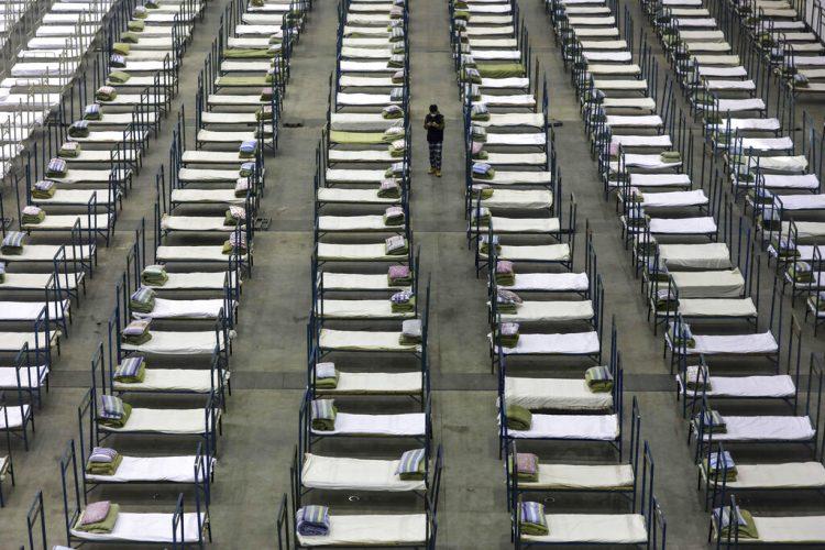El 4 de febrero de 2020 un empleado camina entre camas en un centro de convenciones adaptado para servir como hospital temporal en Wuhan, provincia de Hubei, China. (Chinatopix vía AP)