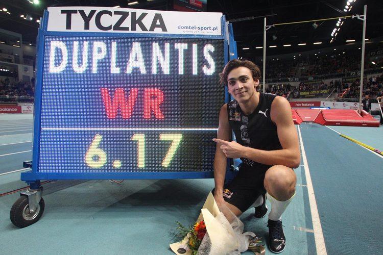 El joven sueco Armand Duplantis posa junto al nuevo récord mundial de salto con pértiga, de 6.17 m, que impuso en Torun, Polonia, el 8 de febrero de 2020. Foto: @WorldAthletics / Twitter.