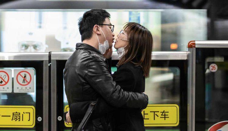 Una pareja se quita las mascarillas de seguridad y se besa mientras espera el transporte público en Shanghái, China. Foto: Liu Xingzhe / EFE: