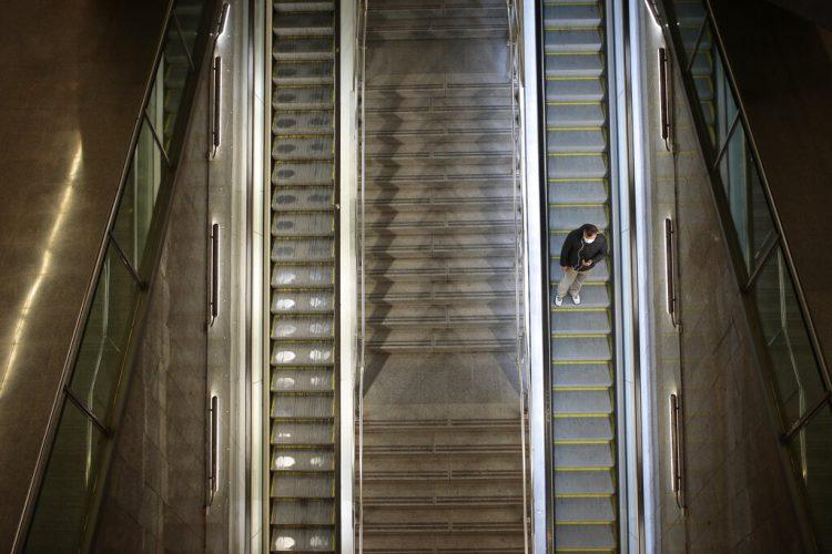 Un hombre sobre la escalera eléctrica de una estación de tren vacía en Barcelona. Foto: Joan Mateu/AP.