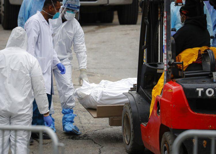 Un cadáver envuelto en plástico es preparado para subirlo con un montacargas al contenedor frigorífico de un camión utilizado como morgue temporal ante falta de espacio por el fallecimiento de personas debido al coronavirus en el Centro del Hospital Brooklyn, en el distrito de Brooklyn, en Nueva York, el martes 31 de marzo de 2020. (AP Foto/John Minchillo)