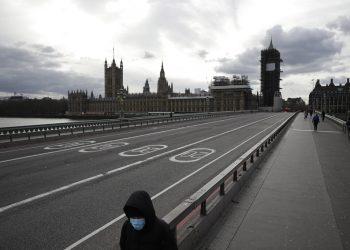Una persona con una mascarilla en el rostro camina por el puente de Westminster casi vacío con el Parlamento al fondo. Londres, viernes 20 de marzo de 2020. Foto: Matt Dunham/AP.