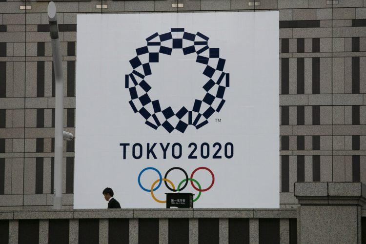 Un hombre pasa junto a un gran cartel promocionando los Juegos Olímpicos de Tokio 2020 en Tokio, marzo de 2020. Foto: AP/Jae C. Hong/Archivo.