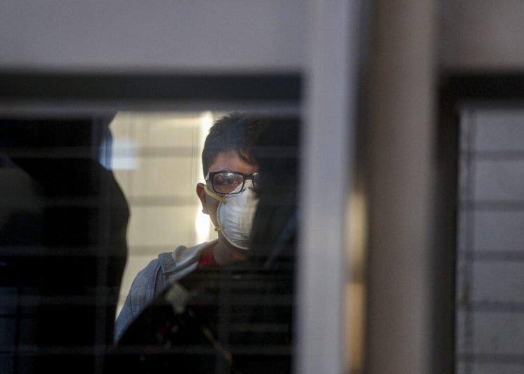Un pasajero con una mascarilla en un elevador antes de abordar un vuelo en el Aeropuerto Internacional Arturo Benítez en Santiago de Chile, 3 de marzo de 2020. Foto: Esteban Félix/AP.