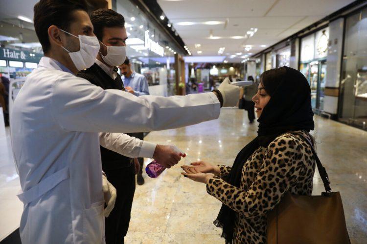 Una mujer se somete a un control de temperatura mientras se desinfecta las manos al entrar al centro comercial Palladium, en Teherán, Irán, el 3 de marzo de 2020. Foto: Vahid Salemi / AP.
