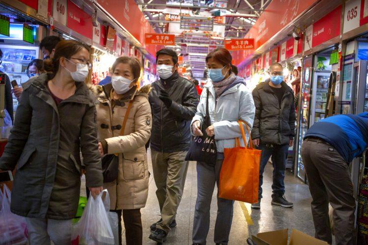 Varias personas con mascarillas compran en un mercado en Beijing, el 14 de marzo de 2020. Foto: AP/Mark Schiefelbein.