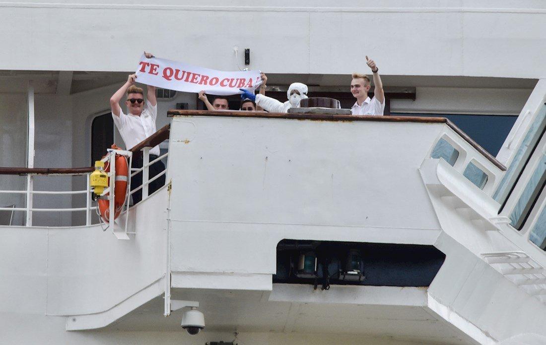 """Varios pasajeros del crucero británico MS Braemar, muestran un cartel de agradecimiento a Cuba durante la operación para su traslado desde el barco en el puerto del Mariel hacia el Aeropuerto Internacional """"José Martí"""" de La Habana, el miércoles 18 de marzo de 2020. Foto: Adalberto Roque / Pool / EFE."""