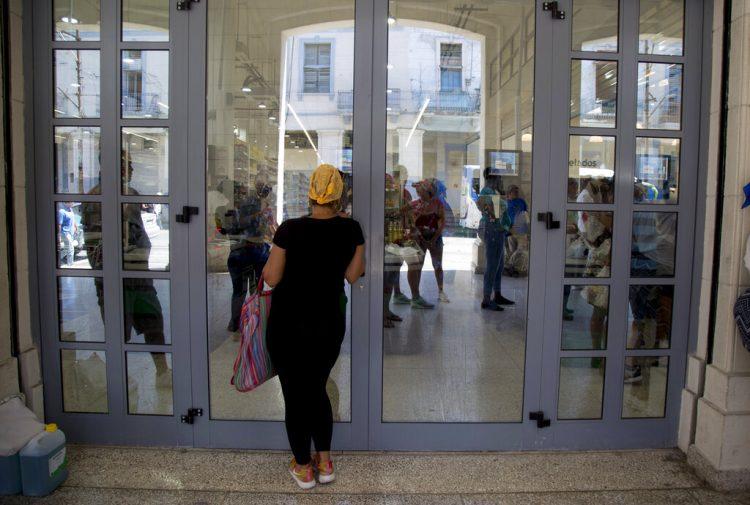 Una mujer inspecciona si hay nuevos productos a la venta en el mercado de 4 Caminos. Foto: AP/Ismael Francisco.