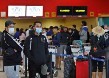 """Varias personas esperan la salida de sus vuelos antes del cierre parcial de las fronteras cubanas para evitar la propagación de la COVID-19, en el Aeropuerto Internacional """"José Martí"""" de La Habana, el 23 de marzo de 2020. Foto: Yander Zamora / EFE."""