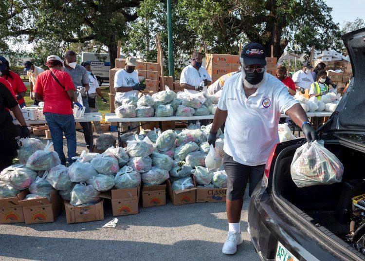 Decenas de voluntarios distribuyen comida gratis a los residente de la ciudad de Opa Lock, una de las urbes más pobres de la zona metropolitana de Miami. | Cristóbal HerreraEFE