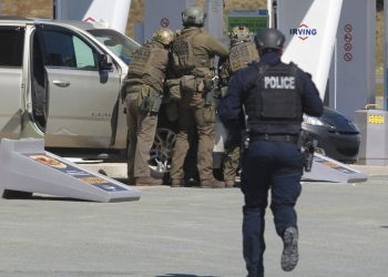 Agentes de la Real Policía Montada de Canadá se preparan para detener a un sospechoso en una gasolinera de Enfield, Nueva Escocia. Foto: Tim Krochak/AP.