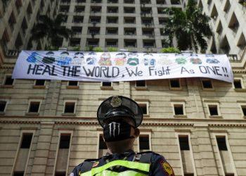 """Un guardia de seguridad de pie ante una pancarta que dice """"Sanen al mundo, luchamos como uno"""", mientras los vecinos aplauden desde las ventanas en homenaje a sanitarios, personal esencial y fuerzas de seguridad, durante una cuarentena impuesta para impedir la expansión del nuevo coronavirus en Manila, Filipinas, el domingo 12 de abril de 2020. (AP  Foto/Aaron Favila)"""