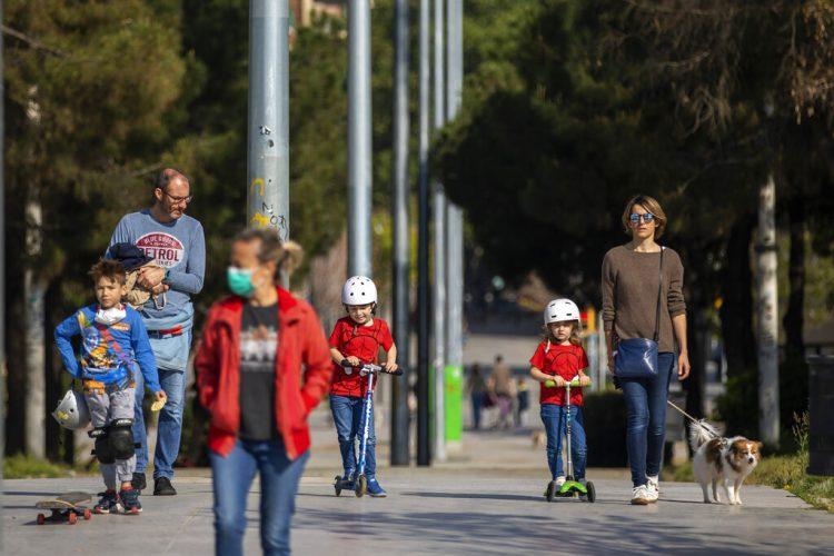 Padres e hijos caminan por un bulevar en Barcelona, España, durante la pandemia de coronavirus en el año 2020. Foto: Emilio Morenatti / AP / Archivo.