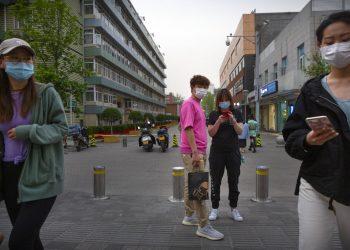 Varias personas cubren sus caras con máscaras como medida contra la propagación del nuevo coronavirus mientras caminan al aire libre por una zona comercial en Beijing, el viernes 24 de abril de 2020.  (AP Foto/Mark Schiefelbein)
