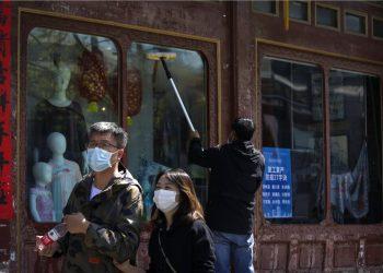 En esta imagen del 12 de abril de 2020, una pareja china camina frente a un trabajador que limpia las ventanas de una tienda de ropa donde se despliegan lineamientos para prevenir la pandemia en la reanudación de labores en Beijing. (AP Foto/Andy Wong)