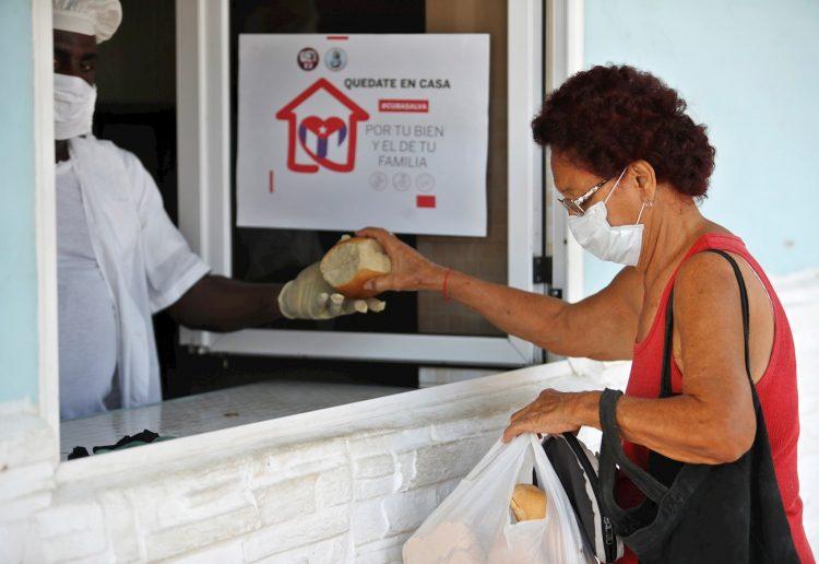 Una mujer con tapabocas compra pan en La Habana. Foto: EFE/Yander Zamora.
