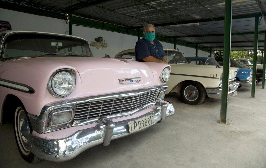 Julio Álvarez posa para una foto con sus automóviles americanos antiguos que los turistas usan para pasear por La Habana, Cuba, el viernes 24 de abril de 2020. Foto: Ismael Francisco / AP.